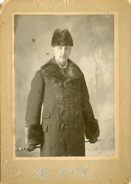 Wessie Newton, as a middle aged man, standing dressed in winter coat trimmed at collar and cuffs ...